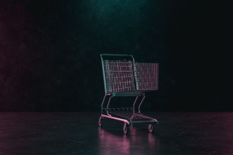 Abandoned shopping cart on table against dark background