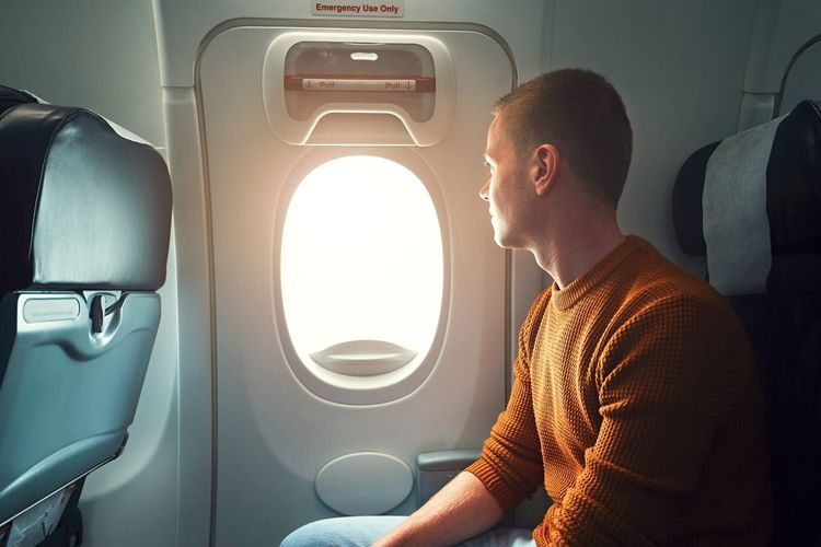 Young man looking through window while traveling in airplane