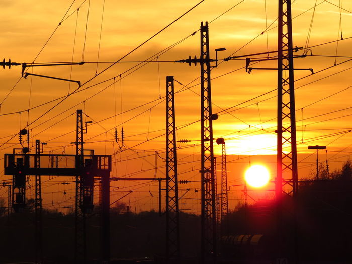 Silhouette Electricity Pylons At Sunset
