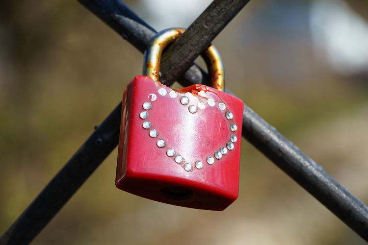 Close-up of red padlock on fence
