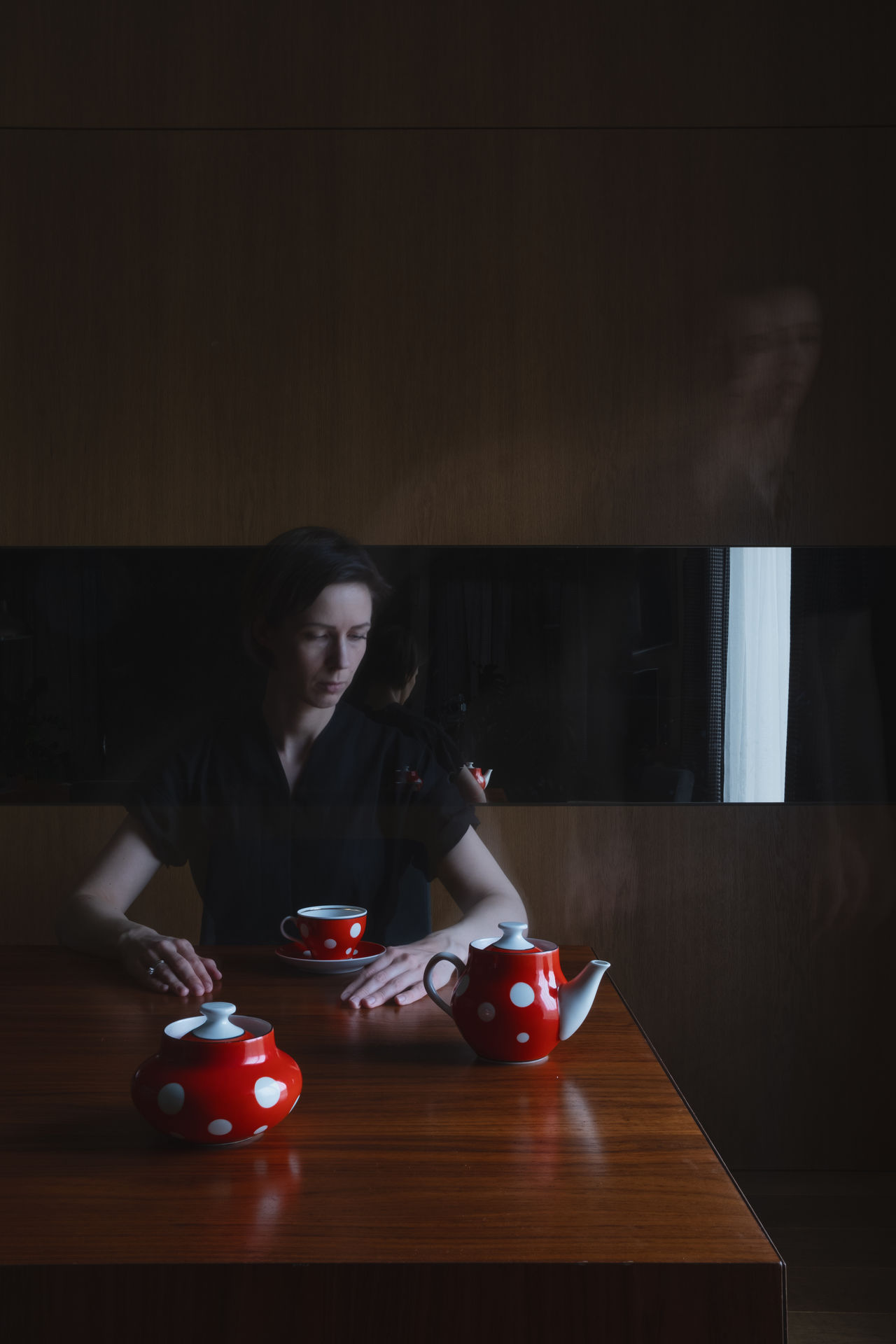 Mid adult woman with coffee on table at home