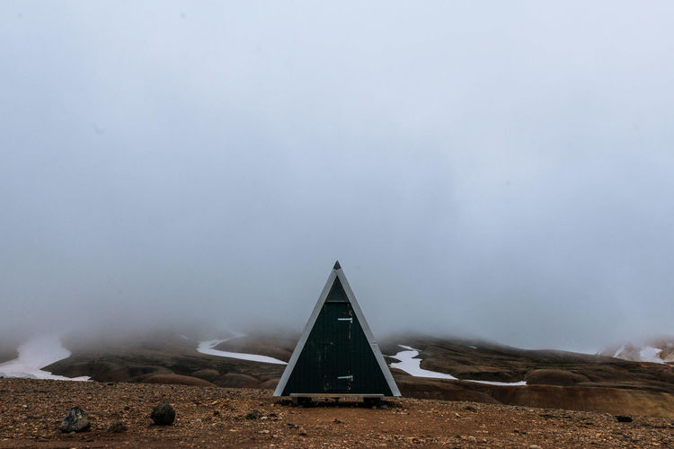Triangle Shape Outhouse On Ground During Foggy Weather