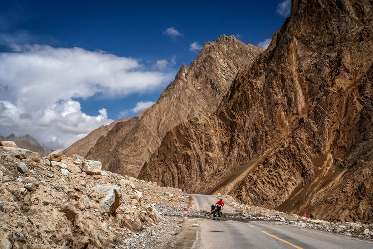People on road by mountain against sky