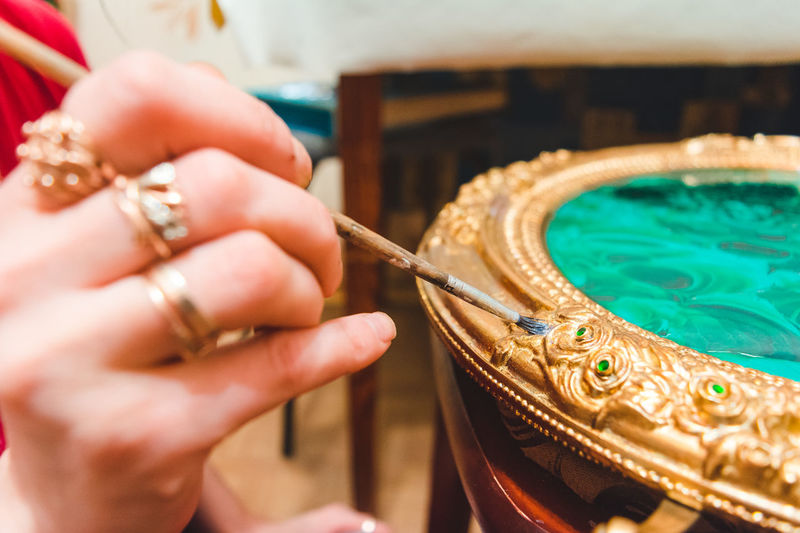 Cropped image of woman painting ornate container
