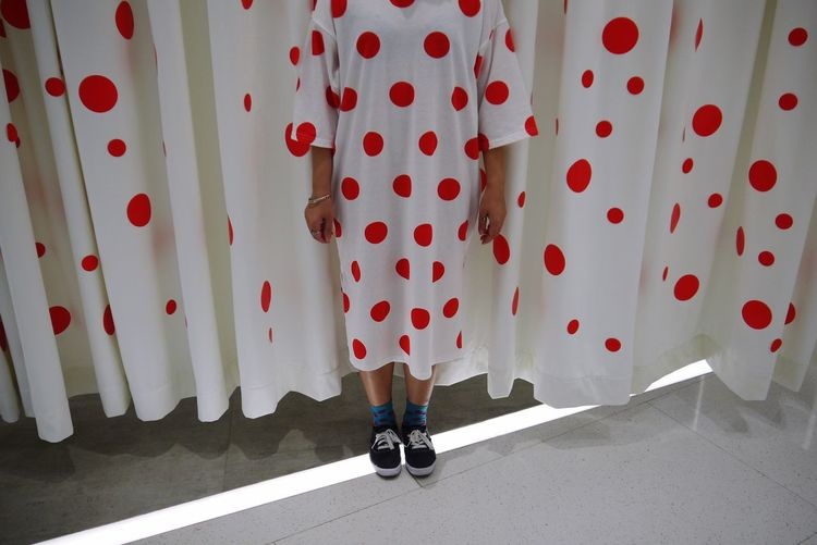Low section of women standing on floor against curtain with polka dots