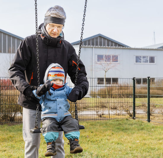 Mature man with toddler girl on swing on playground – Hindeloopen, Netherlands, Europe Care Family Family❤ Grandfather Love Swinging Child Childhood Front View Full Length Generation Gap Generations Girl Granddaughter Help Mature Men Men Offspring Playground Portrait Pushing Swing Toddler  Togetherness Two People