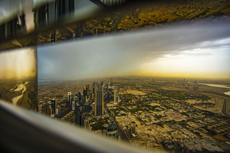 Aerial view of cityscape against sky seen through window during sunset
