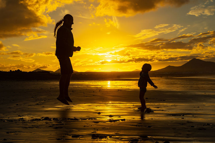 Silhouette father and son at beach against sky during sunset