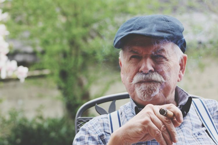 Portrait Of Senior Man Smoking Cigar While Sitting In Yard