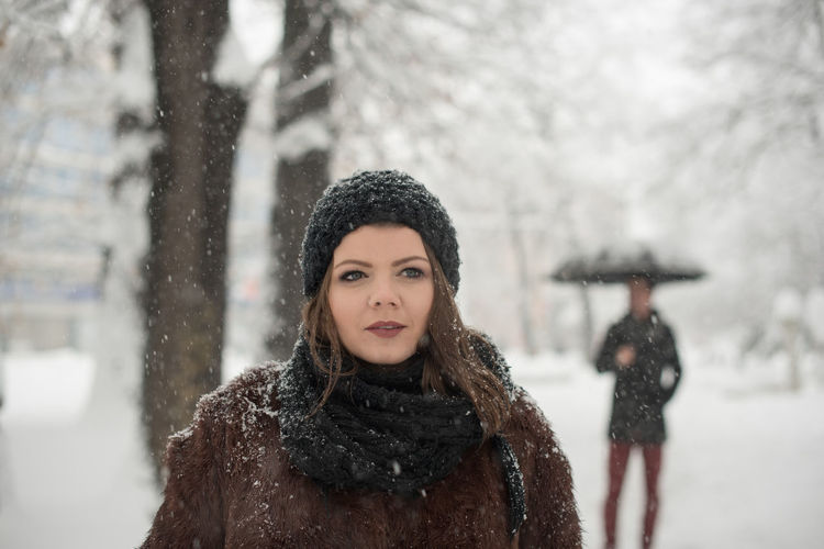 Close-Up Of Young Woman Standing In Snow