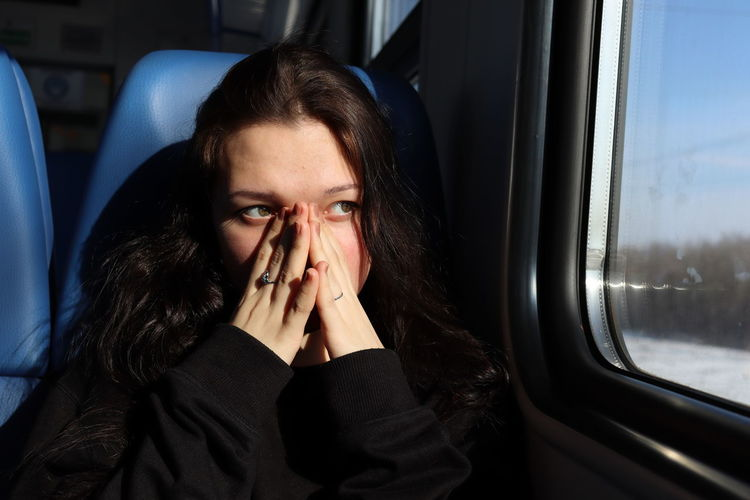 Woman looking away through train window