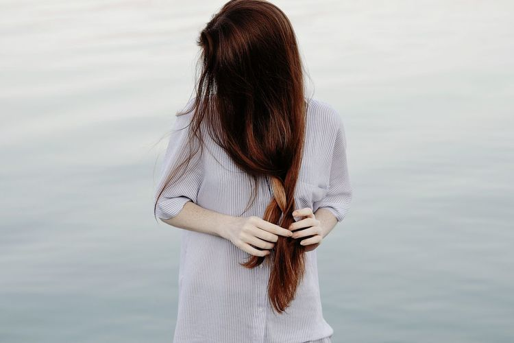 Young woman doing her hair against lake