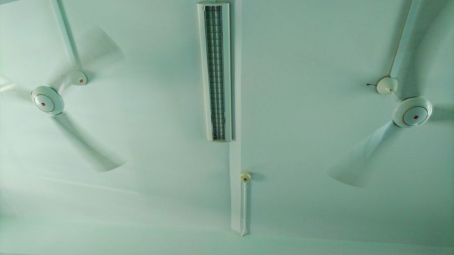 Low angle view of fans and light on ceiling
