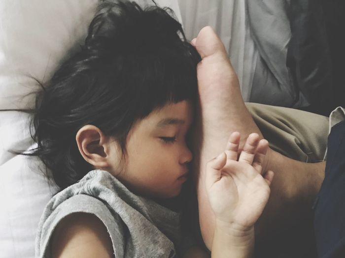 Low section of father with daughter sleeping on bed