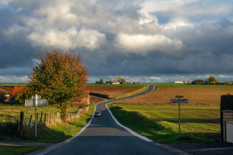 Cloud - Sky Road Sky Transportation Landscape Plant The Way Forward Direction Tree Sign Nature Environment No People Grass Land Day Rural Scene Country Country Road Marking Outdoors Dividing Line