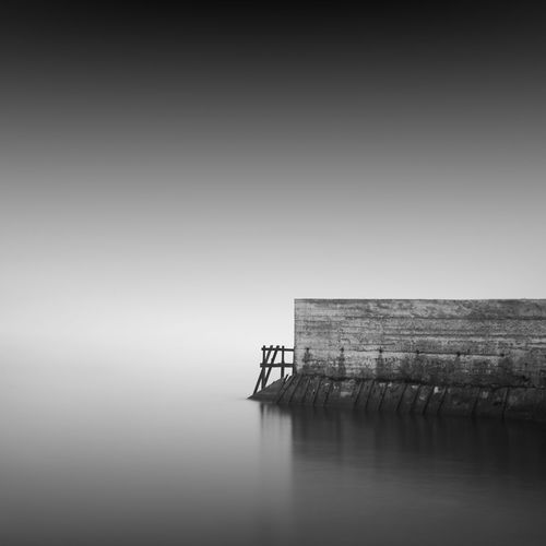 Pier by sea against sky during foggy weather