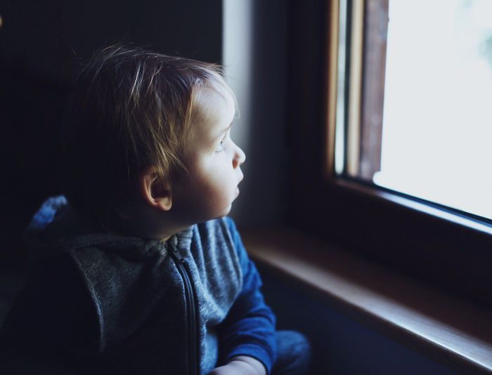 Close-Up Of Boy Looking At Window During Sunny Day
