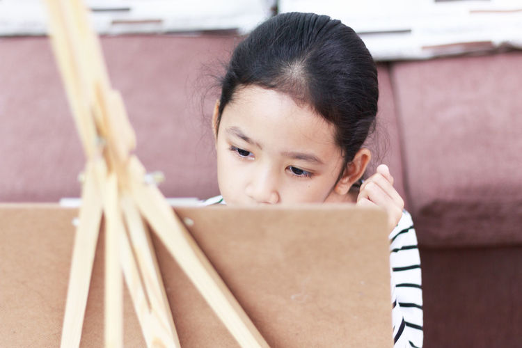 Close-Up Of Girl Painting On Easel