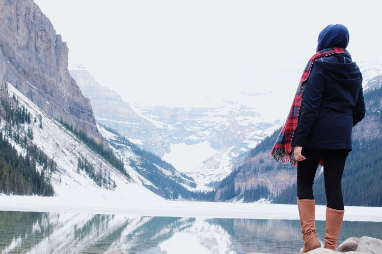 Full Length Rear View Of Woman Standing By Lake Against Snowcapped Mountains