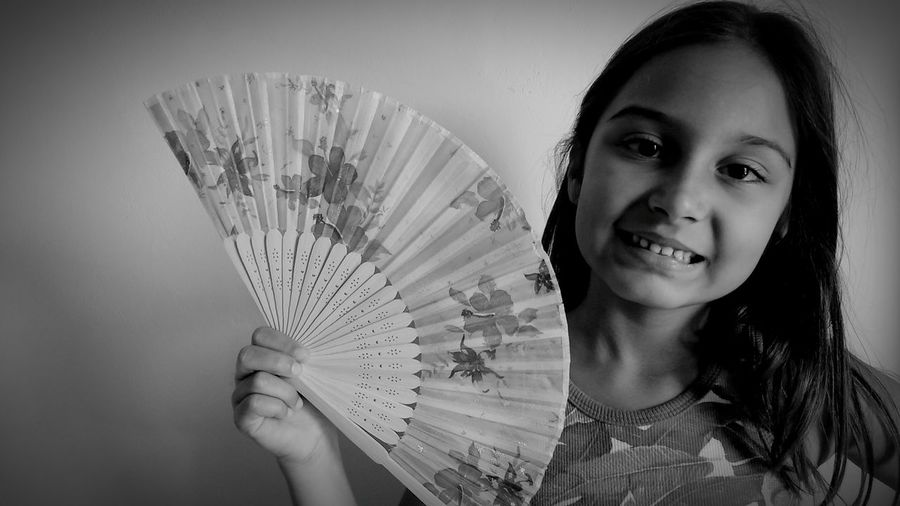 Portrait Of Smiling Girl Holding Folding Fan