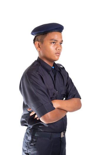Young Asian man in police uniform isolated on white background. White Background Studio Shot Cut Out One Person Clothing Looking At Camera Standing Young Adult Cap Portrait Men Police Officer Security Face Smile Service Occupation Arms Crossed Indoors  Three Quarter Length Hat Confidence  Waist Up Uniform