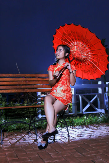 Woman holding umbrella while sitting on bench against sky at night