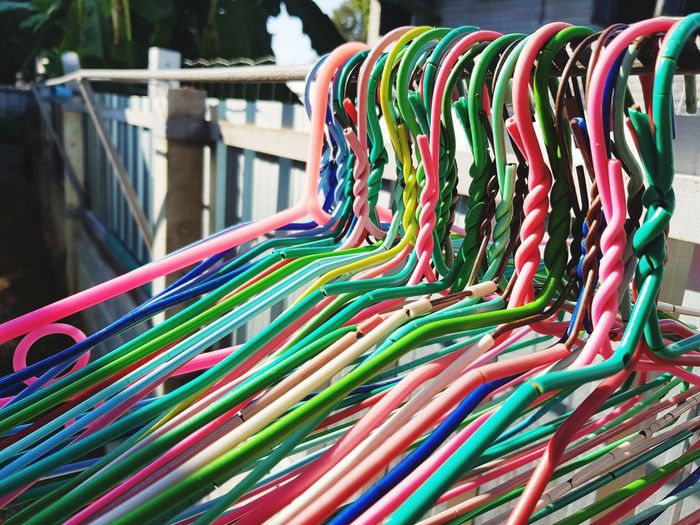 Close-up of multi colored coathangers hanging on rack