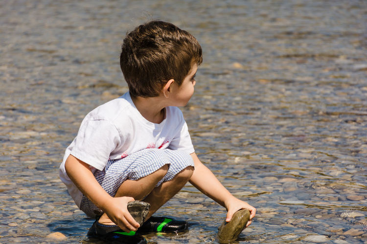 Full length of boy holding stones while crouching at beach