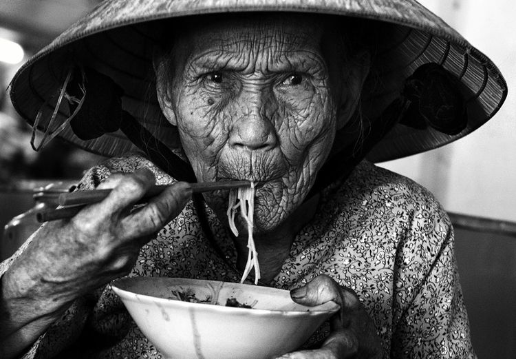Close-up portrait of senior woman eating noodles while sitting at home