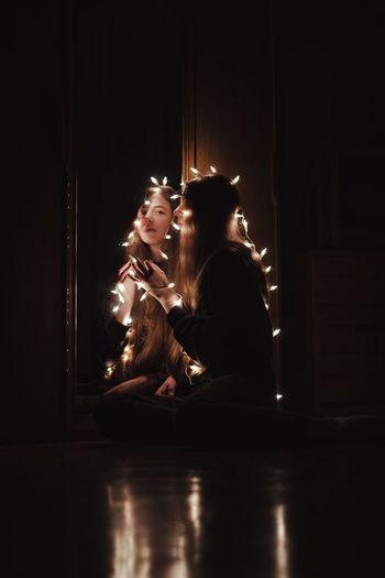 Portrait of girl sitting in illuminated room