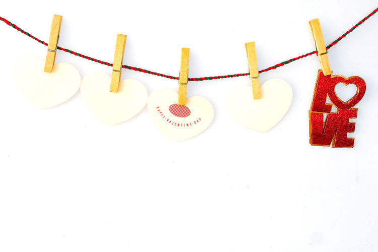 Clothes hanging on rope against white background