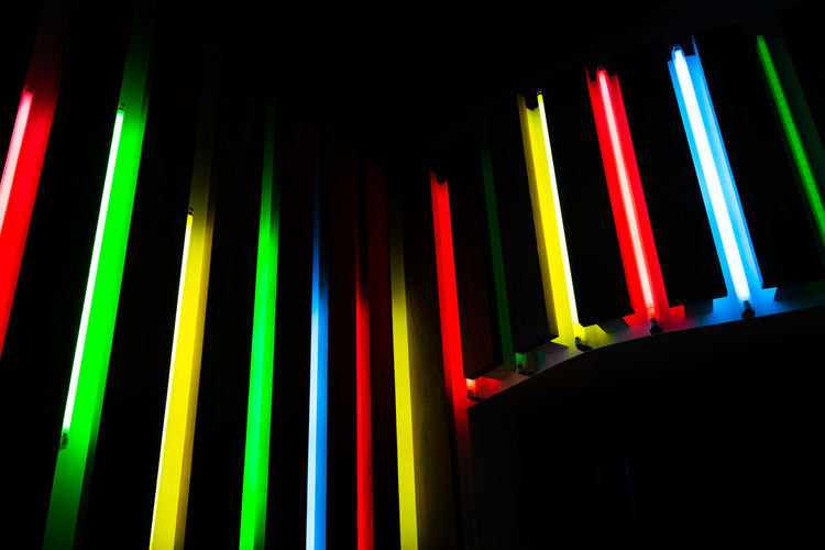 Low angle view of illuminated multi colored lighting equipment in darkroom