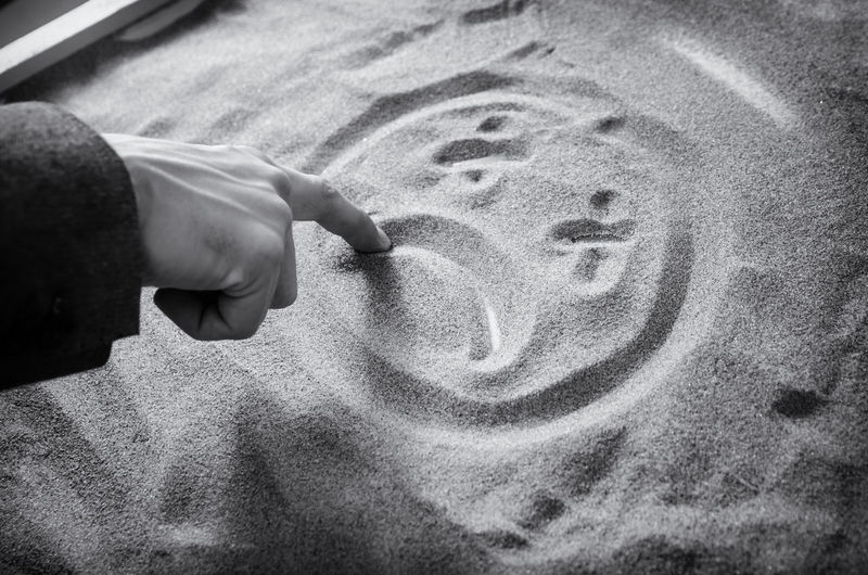 Cropped hand drawing on sand at beach