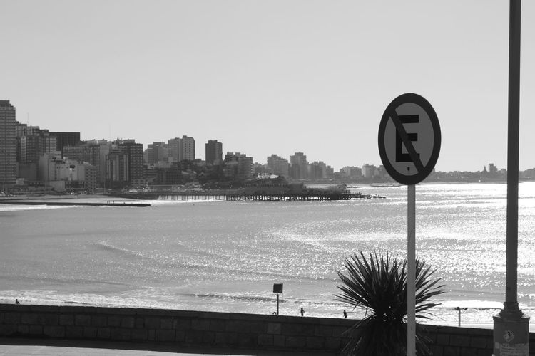 Road sign by sea against buildings in city against clear sky