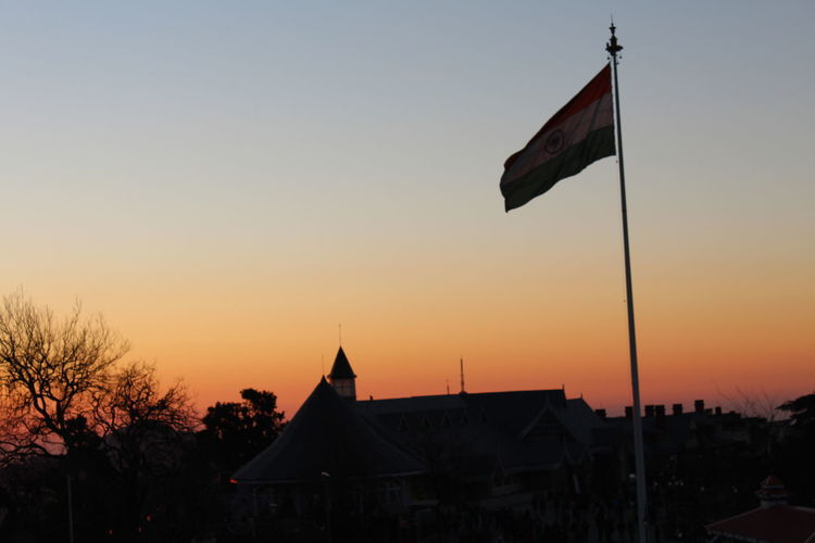 Low angle view of flag on building against sky during sunset