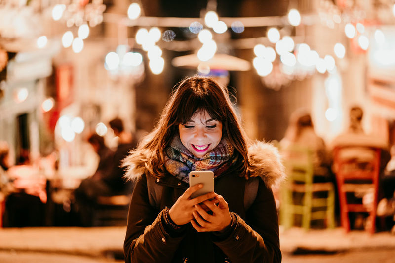 Portrait of young woman using smart phone outdoors