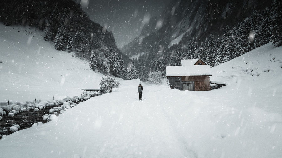 Rear view of woman walking on field against mountains during snowfall