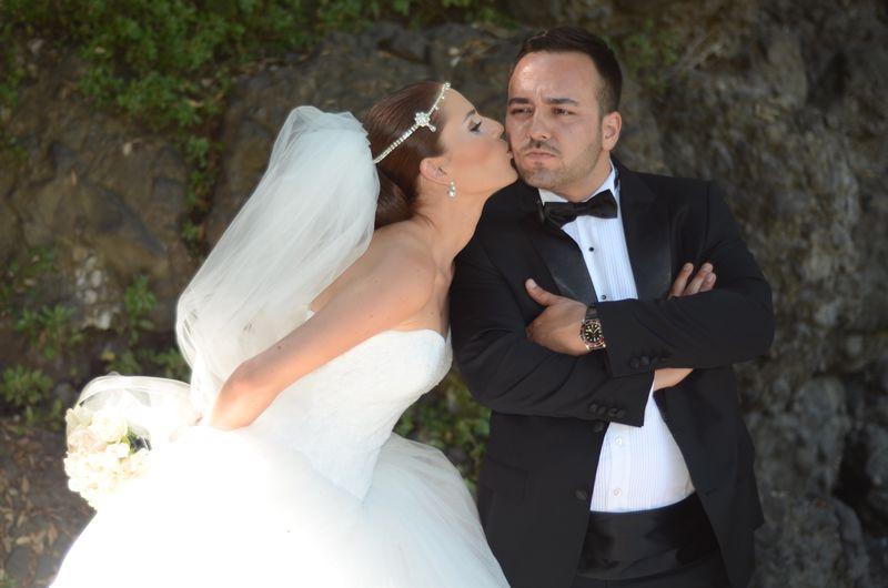 Bride kissing groom against rock formation