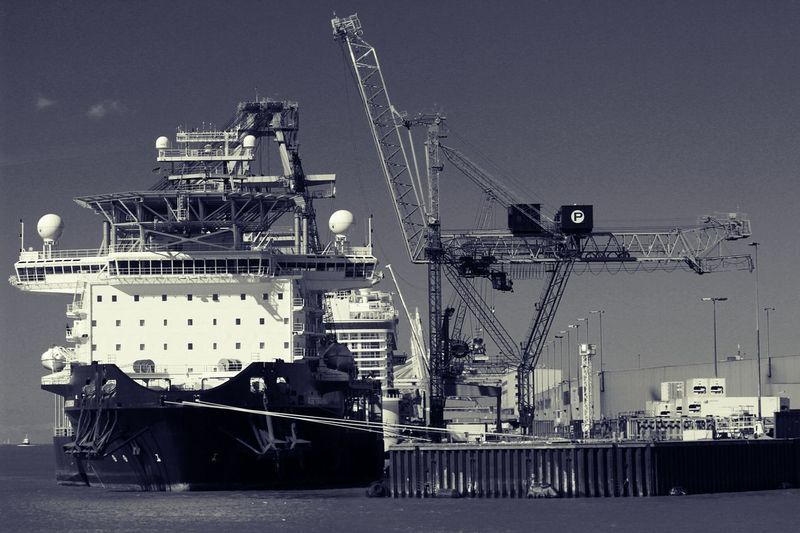 Crane by ship at sea against clear sky