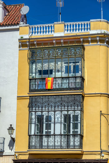 Spanish flag hanging from the balcony of an old yellow building in Seville, Spain Sevilla Seville SPAIN Travel Destinations Travel Tourism Architecture Built Structure No People Europe Historic Andalucía Andalusia Yellow Day City Window Flag Spanish Spanish Flag Building Exterior Building Low Angle View Glass - Material