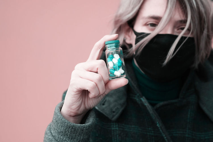 Close-up portrait of woman wearing mask holding capsules against pink background