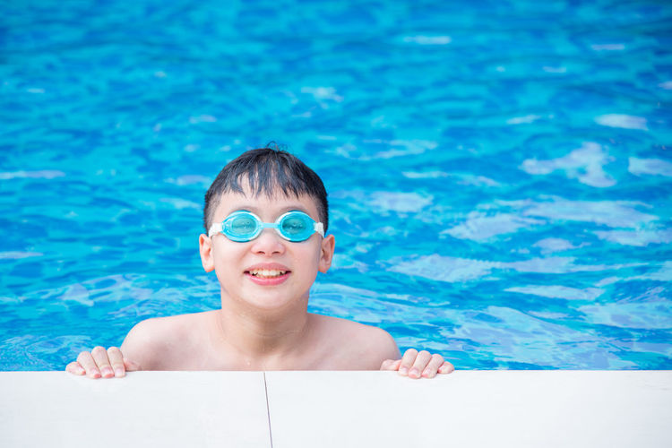 Happy asian boy wearing goggles and smiling at swimming pool Boy Asian  Pool Child Swimming Portrait Swim Playing Happy Young Kid Japanese  Sunny Cute Water Holiday Smile Fun Happiness Joy Vacation Childhood Active Outdoor Sports Blue Summer Swimmer Sport Leisure Youth Activity Wet One Face People Beautiful Lifestyle Cheerful Family Recreation  Chinese Joyful ASIA Thai Korean Goggle