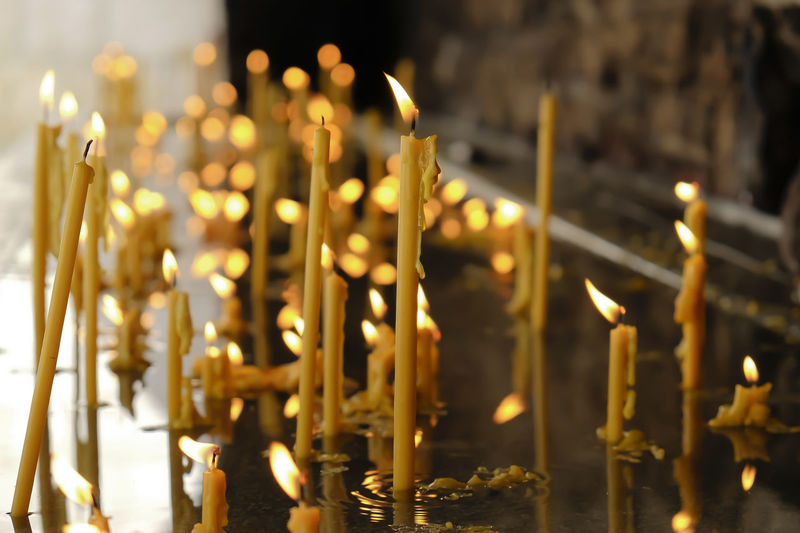 Close-up of illuminated candles in water at church