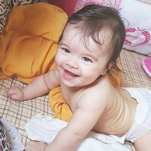 Portrait of cute shirtless baby girl lying on bed at home