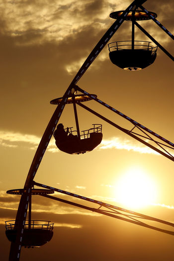 Low Angle View Of Person Sitting In Ferris Wheel Against Sky During Sunset