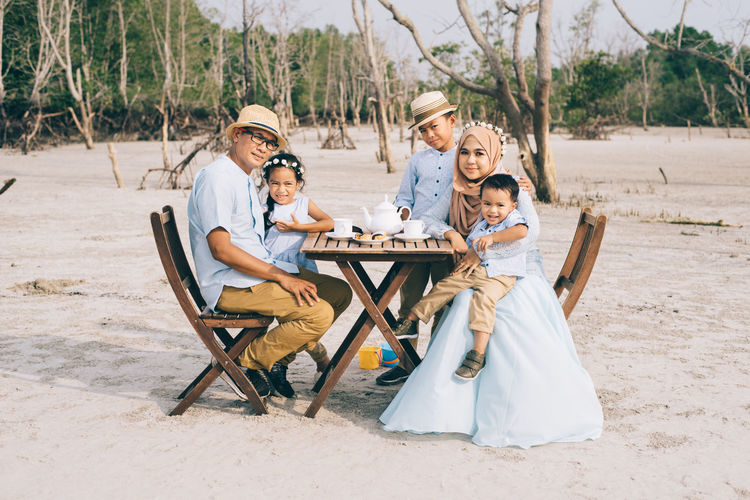 happy asian family having fun picnic outdoors Relationship Love Wood - Material Table Chair ASIA Laughing Picnic Sitting Tree Boys Child Childhood Daughter Emotion Family Girl Group Of People Happiness Hijab Leisure Activity Malaysia Men Muslim Outdoors People Smiling Son Togetherness Women