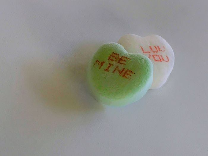 Valentine's Day candy hearts with a message. Valentine's Day  Candy Hearts Candy Heart White Background Message Be Mine Close-up Traditional Heart Candy I Love You Food And Drink Sweetheart Gift No People Green Color Two Hearts