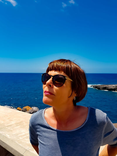Woman Wearing Sunglasses Against Blue Sea