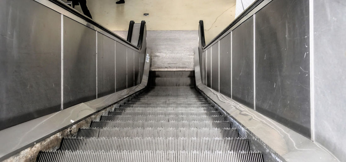 Slightly distorted photo of an escalator, straight view downwards Downwards Stairs Architecture Built Structure Corridor Day Distorted Down Escalator Gray Indoors  No People Steps Steps And Staircases The Way Forward