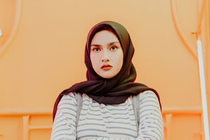 islamic woman confidence starring Portrait Young Women Looking At Camera Headshot Front View Close-up Casual Clothing Yellow Background Brown Eyes Eye Color Natural Beauty Iris - Eye Pink Lipstick  Pretty Graffiti Street Art Eastern European Culture Red Lipstick Eyelid Ceremonial Make-up
